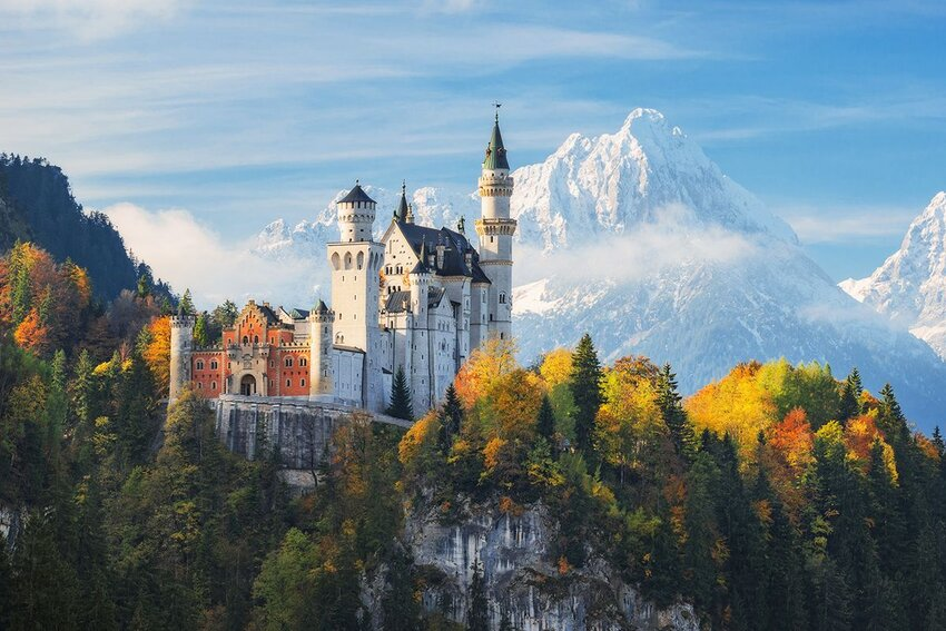 The famous Neuschwanstein Castle with a background of snowy mountains.