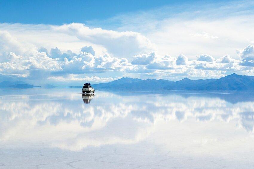 Salar de Uyuni with a car driving in Bolivia.